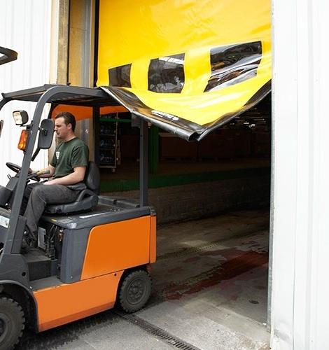 Gele snelroldeur waar een heftruck doorheen rijdt
